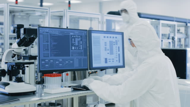 in laboratory over the shoulder view of scientist in protective clothes doing research on a personal computer. modern manufactory producing semiconductors and pharmaceutical items. - bio food video stock e b–roll
