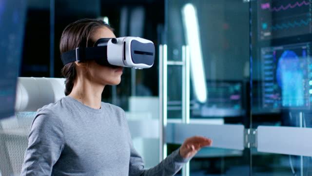 in laboratory scientist wearing virtual reality headset sitting in a chair gesturing at monitors showing brain activity, and neurological data. modern brain study/ neurological research center. - rzeczywistość witrualna filmów i materiałów b-roll
