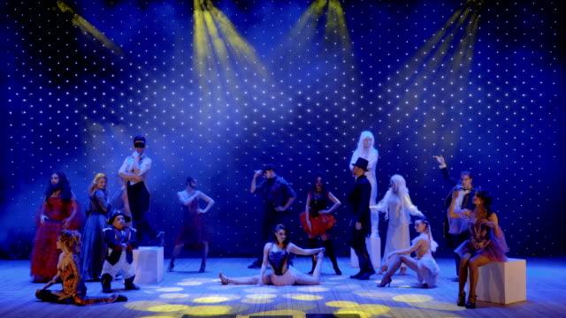 stockvideo's en b-roll-footage met verliefd paar wandelingen tussen mensen en zingt liefdeslied op het podium in theater - vetschmink
