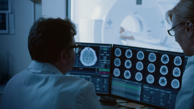vídeos de stock e filmes b-roll de in medical laboratory patient undergoes mri or ct scan procedure, in control room doctor and radiologist discuss diagnosis while watching procedure and monitors brain activity - tumor cerebral