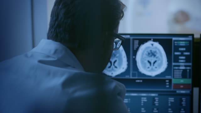 In Medical Laboratory Patient Undergoes MRI or CT Scan Process, in Control Room Doctor Watches Procedure and Monitors with Brain Scans Results. In Medical Laboratory Patient Undergoes MRI or CT Scan Process, in Control Room Doctor Watches Procedure and Monitors with Brain Scans Results. Shot on RED EPIC-W 8K Helium Cinema Camera. radiologist stock videos & royalty-free footage