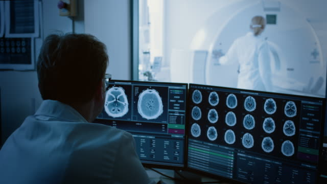 in medical laboratory patient undergoes mri or ct scan process under supervision of radiologist, in control room doctor watches procedure and monitors with brain scans results. - radiografia video stock e b–roll