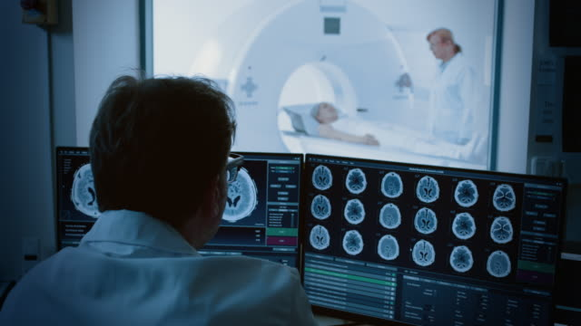 in medical laboratory patient undergoes mri or ct scan process under supervision of radiologist, in control room doctor watches procedure and monitors brain activity. - radiografia video stock e b–roll