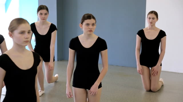 In model school young and beautiful females are standing on knees video