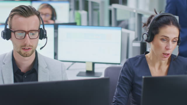 in modern open space office: team of customer support people and salesmen working at their desktop computers, using headsets and making calls, talking to clients, selling insurance - ассистент стоковые видео и кадры b-roll