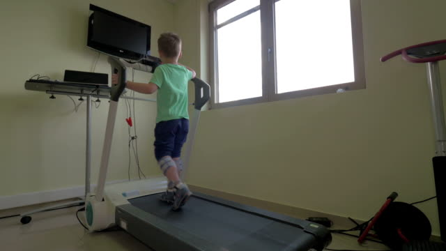 In Nea Kallikratia, Greece in clinic little boy slowly walks on the medical treadmill In Nea Kallikratia, Greece in clinic little boy slowly walks on the medical treadmill. Wellness treatment medevac stock videos & royalty-free footage
