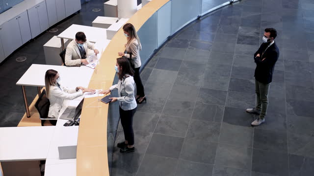 In need of guidelines Formally dressed people are waiting in the line, to fill in forms and check in with their financial advisors. They're keeping a safe distance between them and being as efficient as possible. bank counter stock videos & royalty-free footage