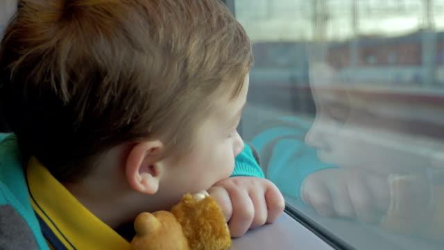 stockvideo's en b-roll-footage met in sint-petersburg, rusland in trein rijdt een kleine jongen die kijkt uit het raam en houdt een stuk speelgoed - raam bezoek