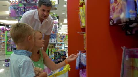 vídeos de stock e filmes b-roll de em busca de um jogo de aprendizagem na loja - brinquedo