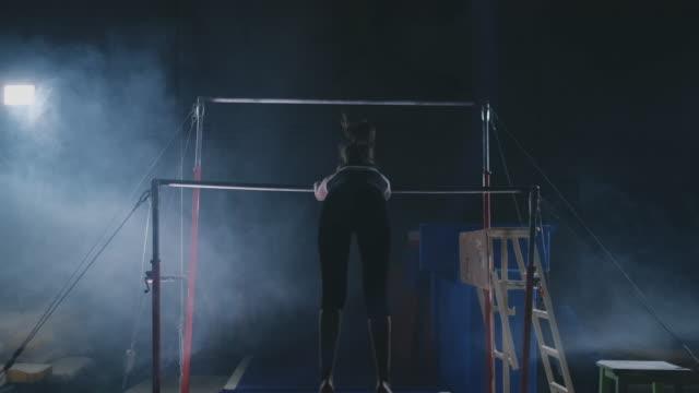 in zeitlupe im rauch mädchen akrobat auf der querlatte führt rotation und springen mit einem coup. wettbewerbe in der gymnastik - turngerät mit holm stock-videos und b-roll-filmmaterial