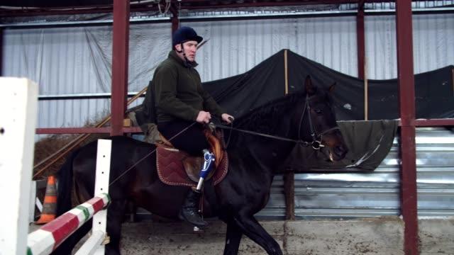 特別な格納庫の黒、サラブレッド馬、乗馬療法に乗る若い男が無効になっているを学習します。男は、彼の右脚ではなく人工的な肢を持っています。動物と障害者のリハビリテーションの概� - 車椅子スポーツ点の映像素材/bロール