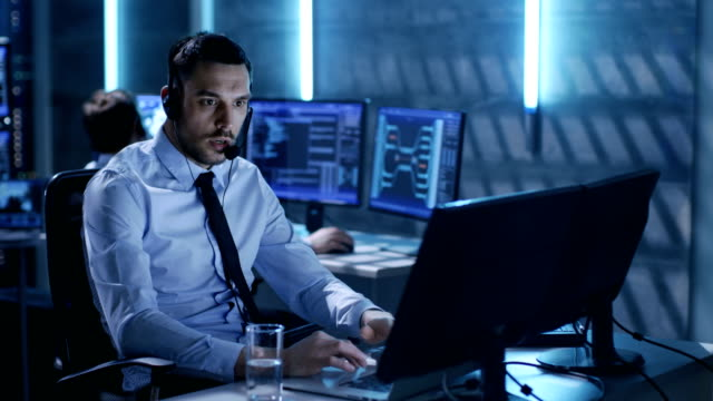 In System Control Center Technical Support Specialist Speaks into Headse while Sitting at His Desk Before Multiple Monitors. His Colleagues are Working in the Background in a Room Full of Displays. video