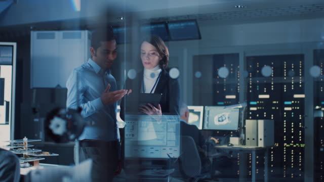 技術研究施設: 女性プロジェクトマネージャーはチーフエンジニアと対話し、タブレットコンピュータを相談します。産業エンジニアチーム、開発者がコンピュータを使ってエンジン設計を� - 研究所点の映像素材/bロール