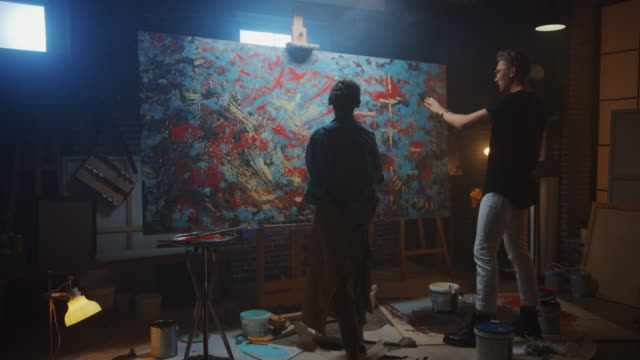 In the Art Class: Talented Young Woman Artist Paints with a Brush on the Large Canvas, Prominent Painter Teaches Her about Styles. Dark Studio with Large Bright Picture full of Color and Emotions