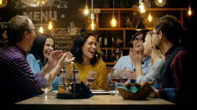 in the bar/ restaurant beautiful hispanic woman shares good news with her dear friends they congratulate her heartily and applaud. they sit in the stylish hipster establishment. - bar video stock e b–roll