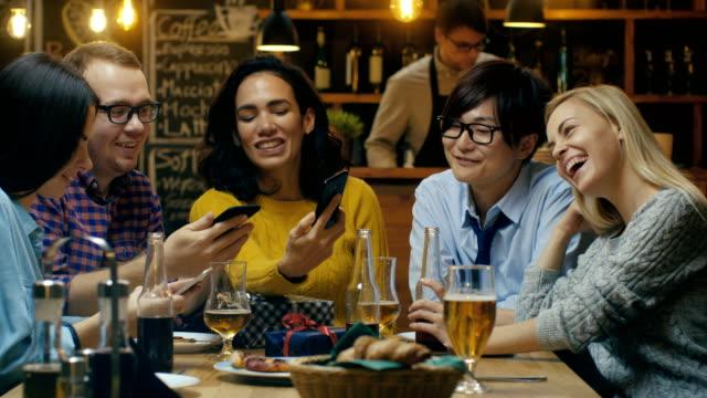 i baren / party restaurang födelsedagsfirande i framsteg vackra unga människor visa sin mobiltelefon skärmar och har kul. - nattliv bildbanksvideor och videomaterial från bakom kulisserna