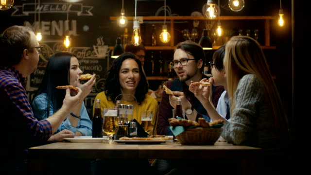 In the Bar/ Restaurant Group of Diverse Young People Eat Slices of Pizza Pie. They Talk, Tell Jokes and Have Fun in This Stylish Establishment. video