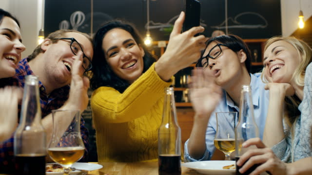 In the Bar/ Restaurant Hispanic Woman Makes Video Call with Her Friends. Group Beautiful Young People in Stylish Establishment. video