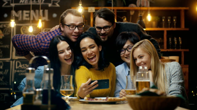 In the Bar/ Restaurant Hispanic Woman Takes Selfie of Herself and Her Best Friends. Group Beautiful Young People in Stylish Establishment. video