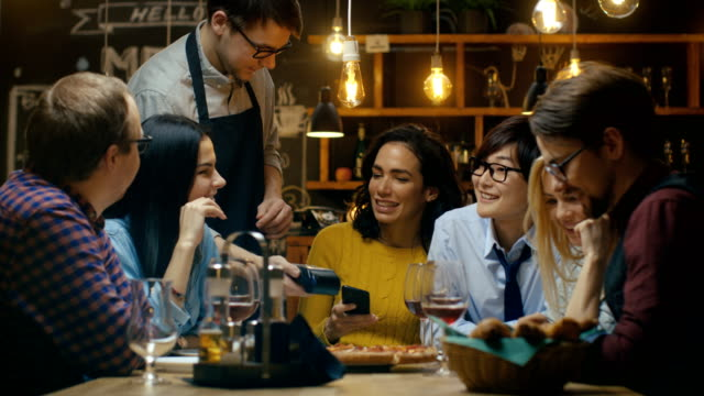 vídeos de stock e filmes b-roll de in the bar waiter holds credit card payment machine and beautiful woman pays for her order with contactless mobile phone payments system. she's surrounded by dear friends and has time of her life. - pagar