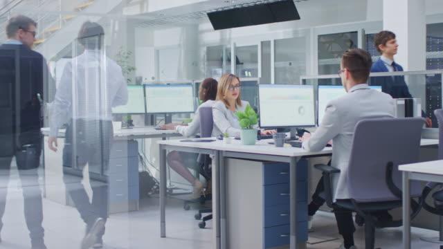 vídeos y material grabado en eventos de stock de en la oficina brillante filas de jóvenes profesionales que trabajan en computadoras de escritorio, hablar, hacer soporte al cliente, comunicarse con los clientes, estadísticas de monitoreo, caminar thorugh pasillo - liado