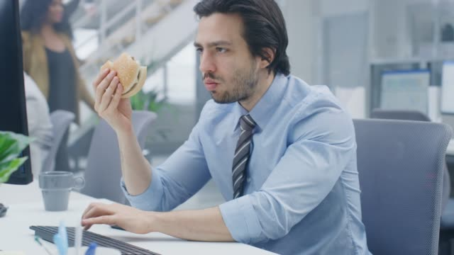 vídeos de stock, filmes e b-roll de no escritório moderno brilhante o homem de negócios novo come o hamburger que senta-se em seu computador de secretária, morde angrily no bolo e continua a trabalhar durante seu almoço. nos colegas de fundo trabalhando - junk food