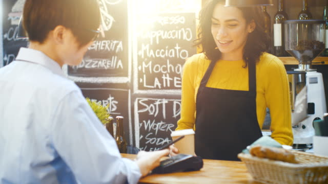 vídeos de stock e filmes b-roll de in the cafe beautiful hispanic woman makes takeaway coffee for a customer who pays by contactless mobile phone to credit card system. - servir comida e bebida
