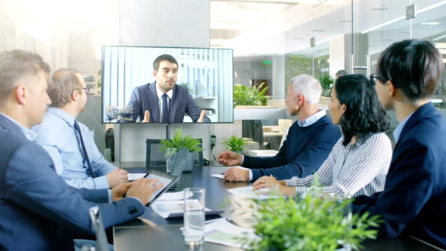 in the conference room board of directors have video call with foreign inverstor. business meeting with big merger discussion. - videoconferenza video stock e b–roll
