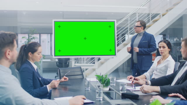 in the corporate meeting room: creative director uses digital chroma key interactive whiteboard for presentation to a board of executives, lawyers, investors. green mock-up screen in horizontal mode - conferenza stampa video stock e b–roll