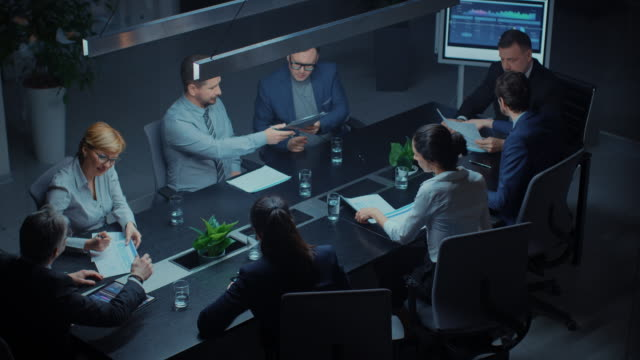 in the corporate meeting room: diverse group of business associates and executivestalking, negotiating, debating, working with documents, planning strategy. late at night in the office. high angle - conferenza stampa video stock e b–roll