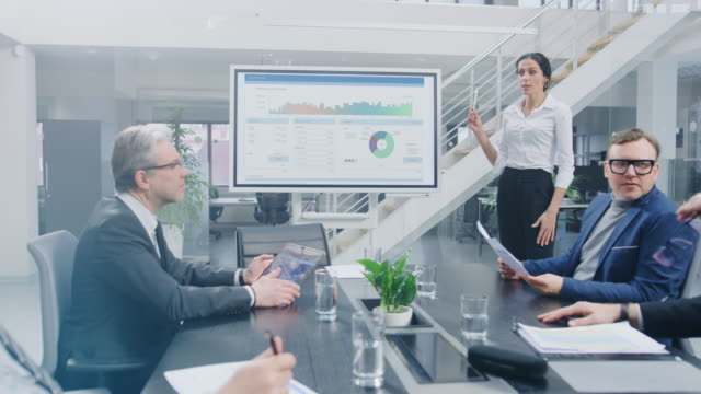 in the corporate meeting room: female analyst uses digital interactive whiteboard for presentation to a board of executives, lawyers, investors. screen shows company growth data with animated graphs - conferenza stampa video stock e b–roll