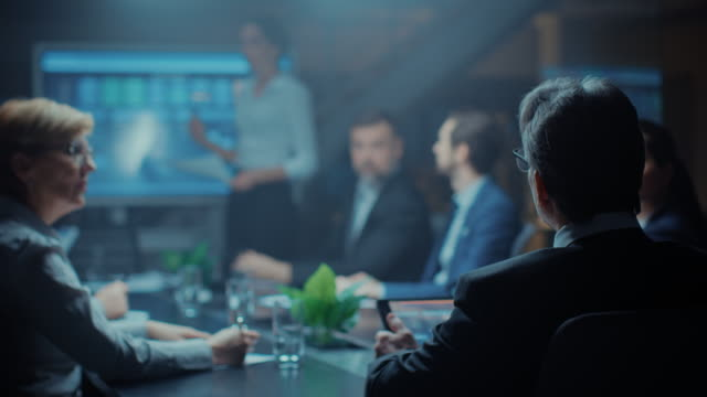 In the Corporate Meeting Room: Female Executive Makes a Speech and Uses Digital Interactive Whiteboard for Presentation to a Board of Directors, Investors. Screen Shows Growth Data. Late at Night Office