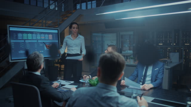 In the Corporate Meeting Room: Female Executive Talks and Uses Digital Interactive Whiteboard for Presentation to a Board of Directors, Investors. Screen Shows Growth Data. Late at Night Office
