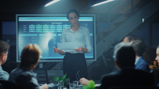 in the corporate meeting room: female project manager points and shows animated graphs and statistics on a digital interactive whiteboard, does talk and presentation for the investors, businesspeople and executives. - conferenza stampa video stock e b–roll