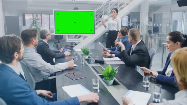 in the corporate meeting room: female speaker uses digital chroma key interactive whiteboard for presentation to a board of executives, lawyers, investors. green mock-up screen in horizontal mode - conferenza stampa video stock e b–roll