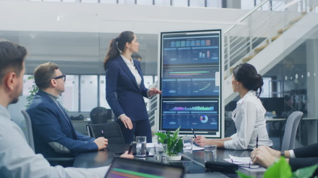 In the Corporate Meeting Room: Young and Ambitious Female Executive Uses Digital Interactive Whiteboard for Presentation and Delivers Passionate Speech to a Board of Executives, Lawyers, Investors