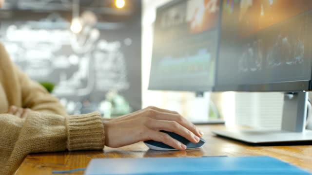 女性の手を使用してマウスとパソコンは入力のクリエイティブエージェンシーのクローズ アップ。バック グラウンドで彼女の同僚とのプロジェクトに取り組んでいます。 - 編集者点の映像素材/bロール