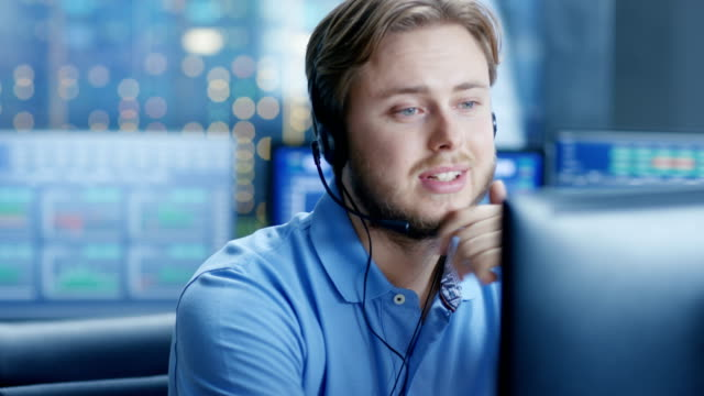 In the Customer Support Center Representative Makes Calls and Talks with Customer Through the Headset.