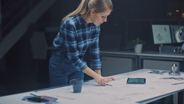 nella struttura di ingegneria del design industriale scuro: l'ingegnere femminile lavora con i progetti posati su un tavolo, utilizza tablet digitale e bevande caffè. sui disegni desktop e sui componenti del motore - architetto video stock e b–roll