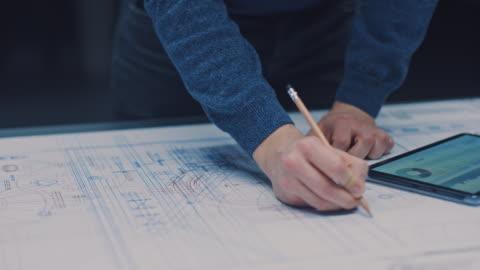 vidéos et rushes de dans l'installation d'ingénierie de conception industrielle sombre: ingénieur mâle travaille avec des blueprints posant sur une table, utilise le crayon, la règle et la tablette numérique. sur le bureau plusieurs dessins. focus sur les mains - bureau ameublement