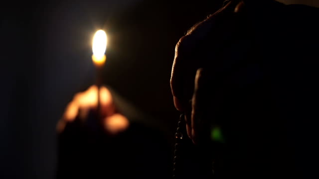 In the dark the Monk prays holding a candle and a rosary in his hand