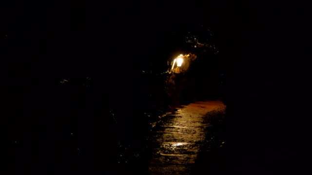 In the dark tunnel woman is walking towards exit