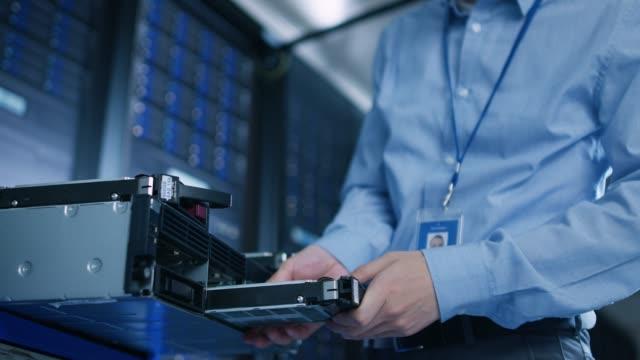 i datacentret: it-ingenjör installerar ny hdd hårddisk och annan hårdvara i servern rack utrustning. it-specialist göra underhåll, kör diagnostik och uppdatera maskinvara. låg vinkel. - server room bildbanksvideor och videomaterial från bakom kulisserna