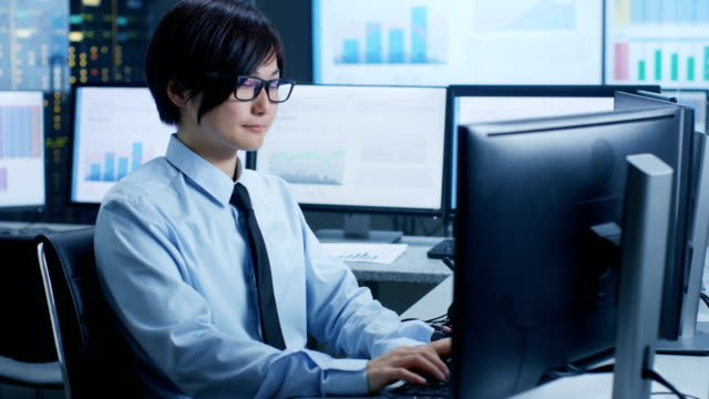 In the Data Mining Center Statistician sits at His Workstation Surrounded with Monitors Displaying Data and Graphs.