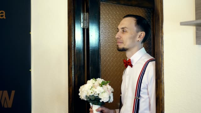 in the doorway the young guy comes in, the groom, in a red bow tie and with a bouquet of flowers. he looks at the bride