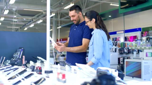vídeos de stock, filmes e b-roll de na loja de eletrônicos lindo casal jovem olha mais recente computador tablet, eles pensam em comprar um. loja é grande, brilhante e tem todos os novos dispositivos. - loja