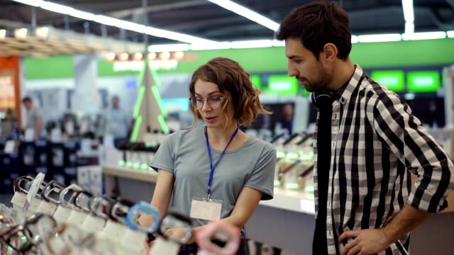 In the electronics store female consultant gives professional advice to a young man. He considers to buy a new smartphone and needs expert opinion. Store is modern, bright and has all the new devices. Blurred background video