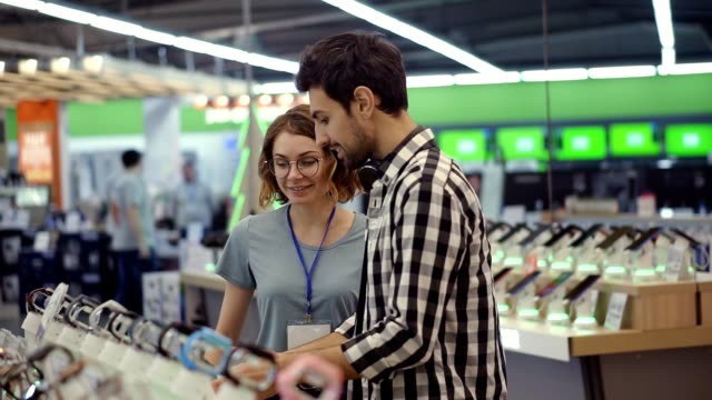 In the electronics store female consultant gives professional advice to a young man. He considers to buy a new smartphone and needs expert opinion. Store is modern, bright and has all the new devices. Blurred background. Slow motion video