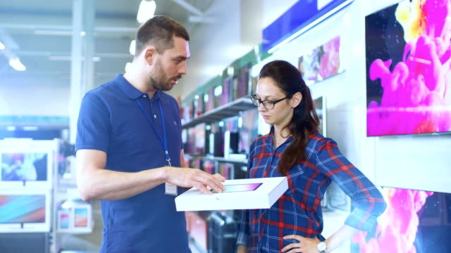 in the electronics store professional consultant provides expert advice on tablet computer specifications for beautiful young woman. store is bright, modern and has all the latest devices. - modella negozio video stock e b–roll