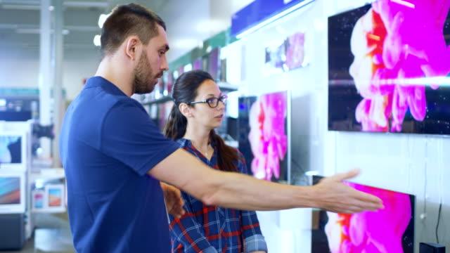電器店では、プロのコンサルタントは、買うために新しい 4 K UHD テレビの見える若い女性に専門家のアドバイスを提供します。この明るい現代の格納すべて、最新テレビ モデルぶら下がっている壁に。 ビデオ